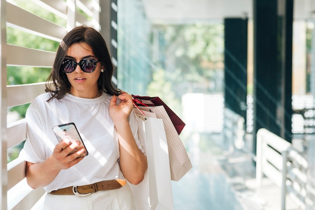 Middellange geschotene vrouw die op de telefoon kijkt