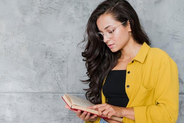 Middellange geschotene vrouw met glazen het lezen