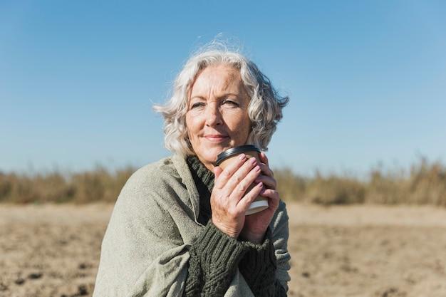 Middellange geschotene vrouw met koffie op het strand