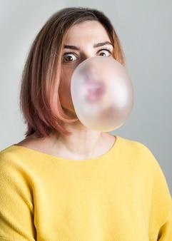 Middellange geschotene vrouwen blazende kauwgom