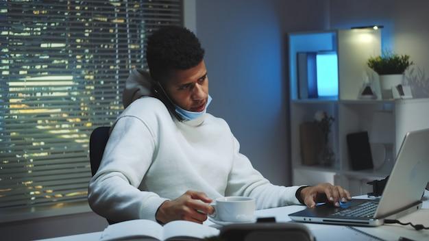 Middellange opname van gemengd ras man aan het werk op de computer, spreken door smartphone en het drinken van een kopje thee