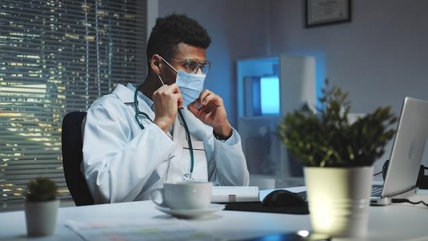 Middellange opname van jonge afrikaanse arts die laat zien hoe een medisch masker te dragen door een videogesprek op de computer