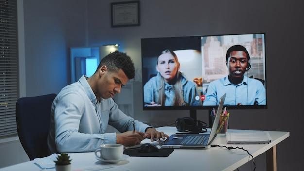 Middellange opname van jonge afrikaanse chief manager die videogesprek voert op grote monitor met collega's in quarantaine