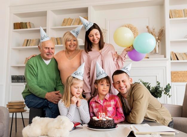 Middellange schot gelukkige familie poseren met cake Gratis Foto