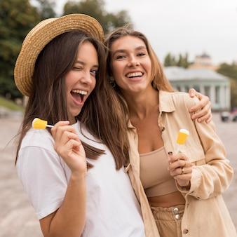 Middellange schot gelukkige meisjes poseren met snoep
