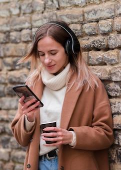 Middellange schot jonge blonde vrouw luisteren naar muziek op de koptelefoon