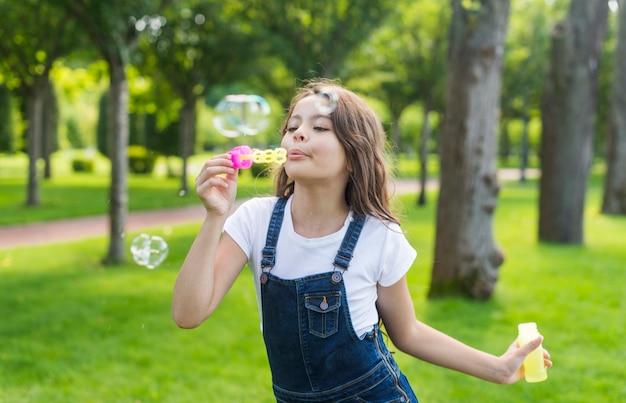 Middellange schot schattig klein meisje zeepbellen maken