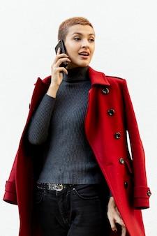 Middellange schot van mooie vrouw die bij telefoon spreekt