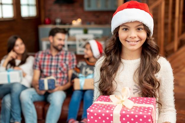 Middellange shot gelukkig meisje met hoed en cadeau