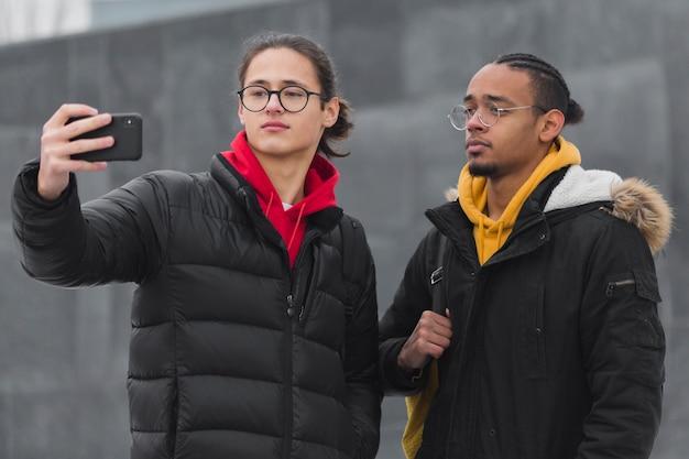 Middellange shot jongens die een selfie maken