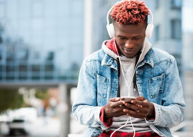 Middellange shot man met smartphone en witte koptelefoon