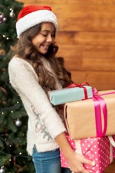 Middellange shot meisje met geschenken in de buurt van de kerstboom