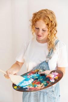 Middellange shot meisje met schilderij items