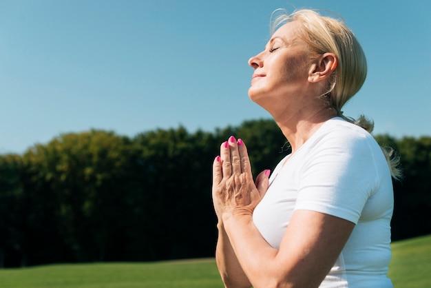 Middellange shot oude vrouw mediteren