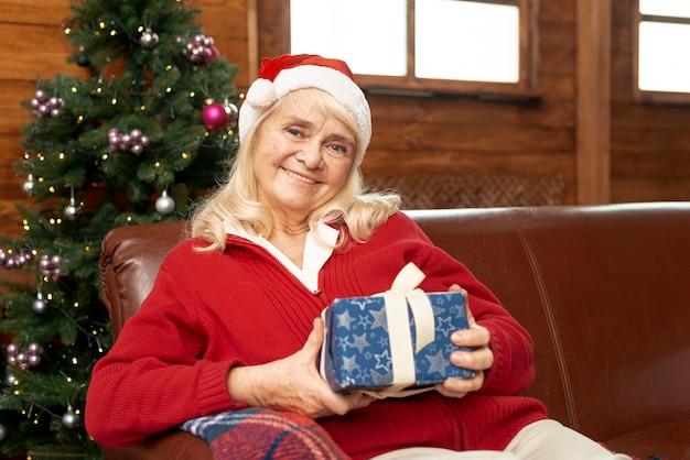 Middellange shot oude vrouw met cadeau