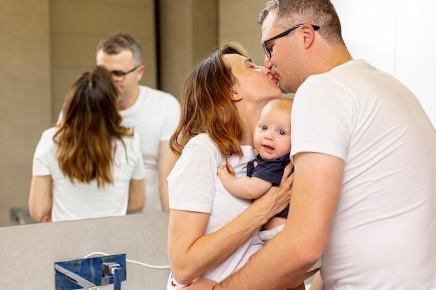 Middellange shot ouders kussen in de badkamer