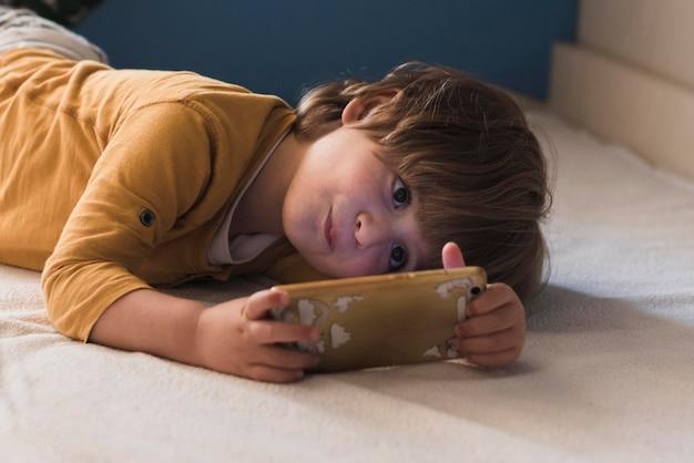 Middellange shot schattige jongen op smartphone
