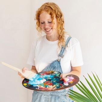 Middellange shot smiley meisje houden schilderij palet