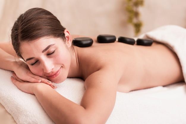 Middellange shot smiley meisje probeert stenen spa-behandeling