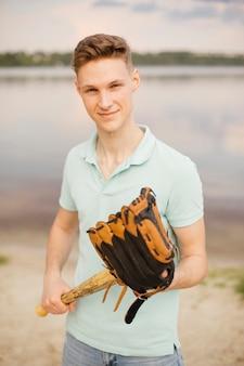 Middellange shot smiley tiener met honkbal apparatuur