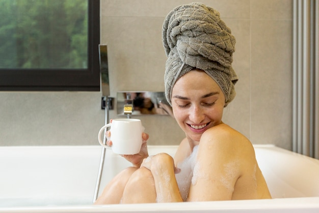 Middellange shot smiley vrouw in de badkuip
