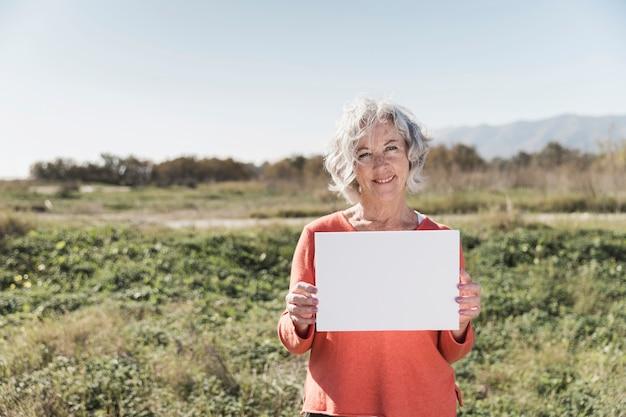 Middellange shot smiley vrouw met een stuk papier