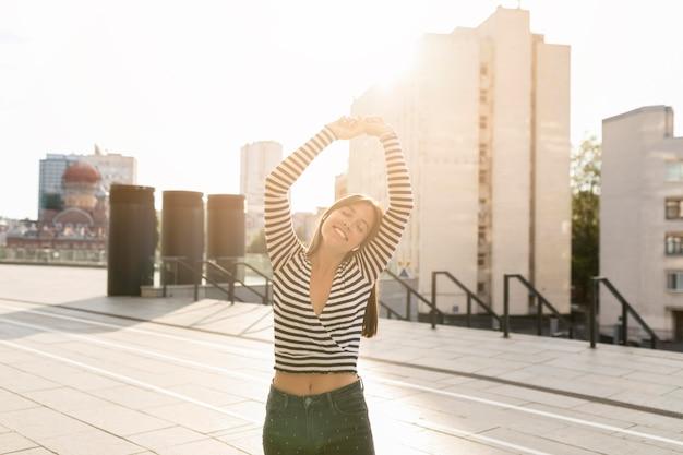 Middellange shot smiley vrouw poseren op zonlicht