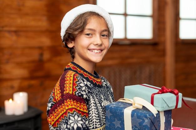 Middellange shot smileyjongen met geschenken