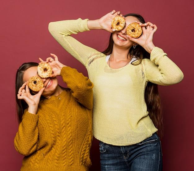 Middellange shot smileymeisjes met donuts