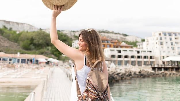 Middellange shot toeristische poseren met hoed