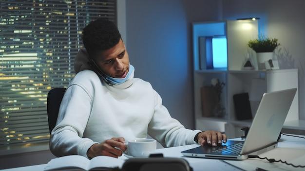 Middellange shot van man aan het werk op computer, spreken door smartphone en het drinken van een kopje thee