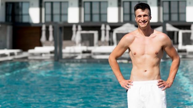 Middellange shot van mooie man bij zwembad