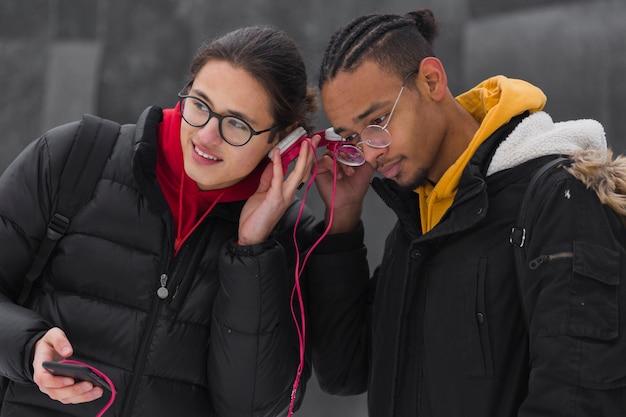 Middellange shot vrienden buitenshuis luisteren naar muziek
