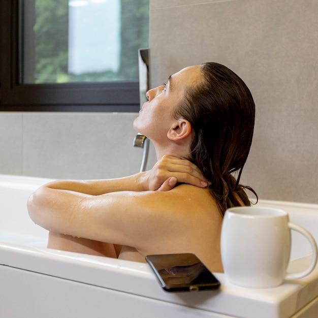 Middellange shot vrouw in badkuip met smartphone