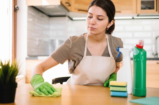 Middellange shot vrouw schoonmaak tafel