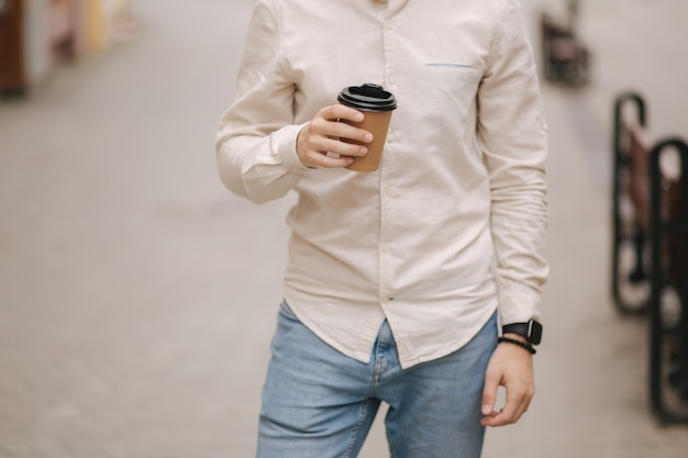 Middelste selectie van man staan in de stad met een kopje koffie.