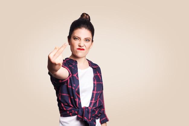 Middelvinger teken. ongelukkige boze jonge vrouw die middelvinger met ontevreden gezicht toont. studio-opname op beige achtergrond. focus op gezicht.