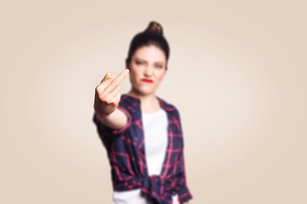 Middelvinger teken. ongelukkige boze jonge vrouw die middelvinger met ontevreden gezicht toont. studio-opname op beige achtergrond. focus op vingers.