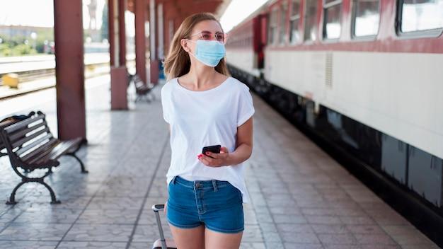 Midden geschoten meisje dat met masker langs trein loopt