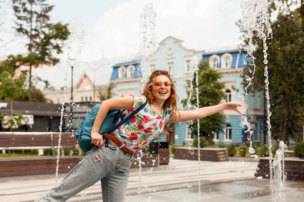 Midden geschoten vrouw poseren in de buurt van fontein