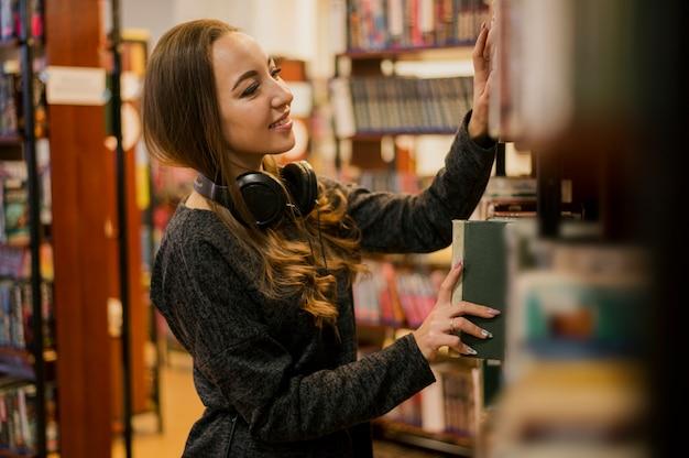 Midden geschotene vrouw die hoofdtelefoons draagt rond de hals die boek op plank zet