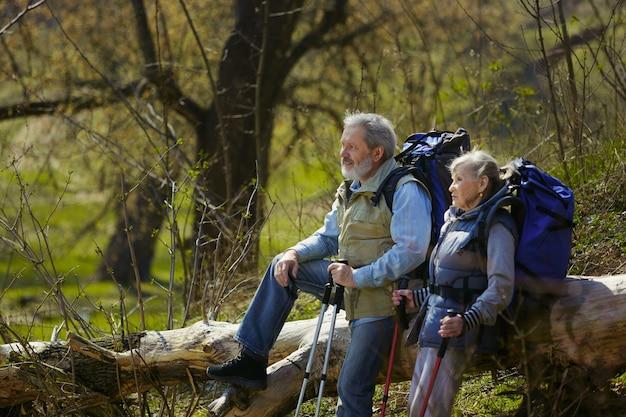 Midden in de natuur. leeftijd familie paar man en vrouw in toeristische outfit wandelen op groen gazon in de buurt van bomen in zonnige dag. concept van toerisme, gezonde levensstijl, ontspanning en saamhorigheid.