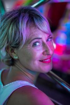 Midden leeftijd glimlachende vrouw die bij gloeiende lampen benieuwd zijn