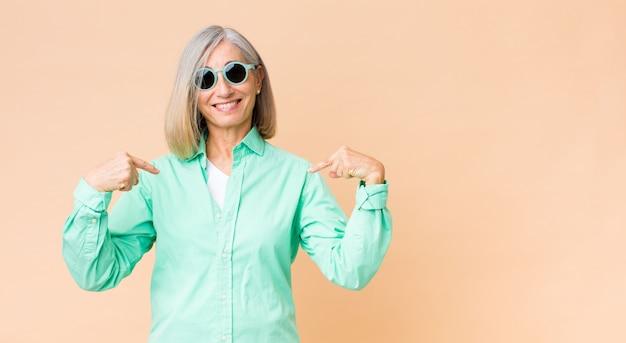 Midden leeftijdsvrouw die zonnebril op exemplaar ruimtemuur draagt