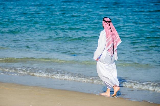 Midden-oosten manier geklede arabische man vormt voor de kust.