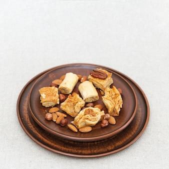 Midden-oosters gebakje van phylo (filo) deeg en noten en honing. kleischotel met snoepjes