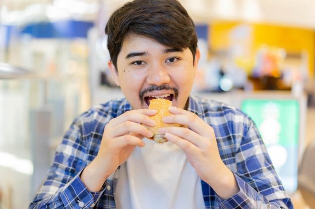 Midden-oosterse man bijt hamburger om te eten in brunchmaaltijd in restaurant met geluk in ontspanningstijd