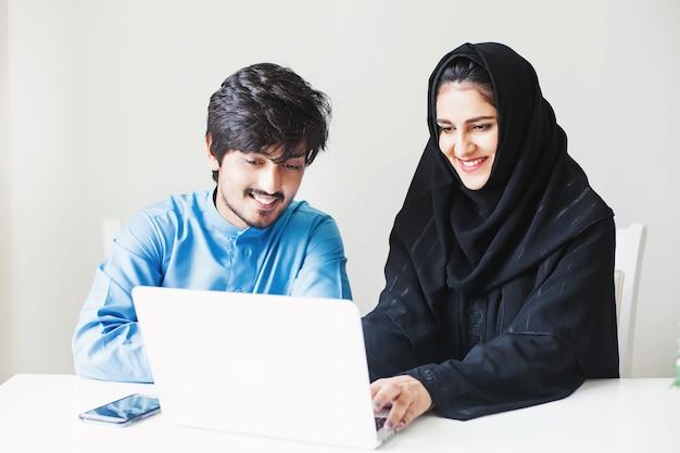 Midden-oosterse moslimvrouw en man werken samen aan een laptop