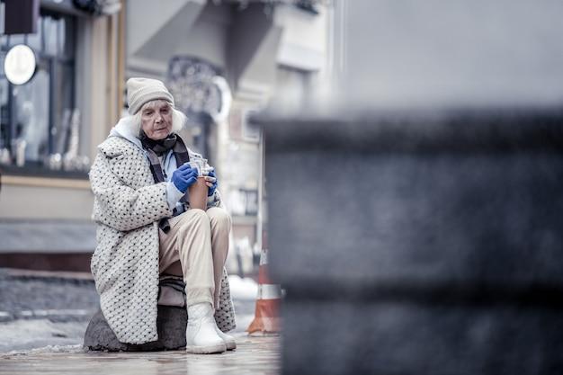 Midden op straat. trieste ongelukkige vrouw zittend op de steen midden op straat terwijl ze om geld bedelde