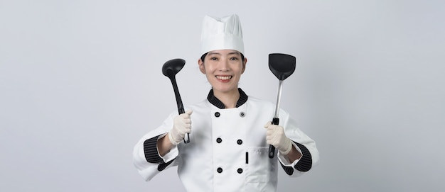 Midden oud van aziatische de holdingskeukengerei van de vrouwenchef-kok
